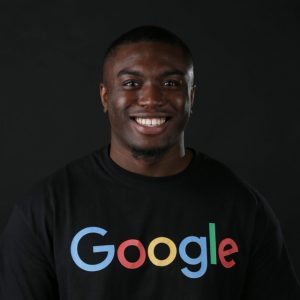 Van Dennis is an African American man wearing a black t-shirt that says Google on it. He looks directly at the camera and smiles.