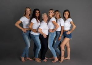 6 women of various sizes, shapes, and races stand in a line wearing a white top and jeans.