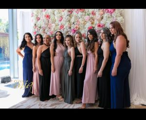 9 women wearing full length gowns pose in front of a white and pink flower wall.